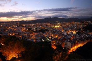 Vue sur Malaga illuminée au crépuscule depuis les remparts du Castillo de Gibralfaro
