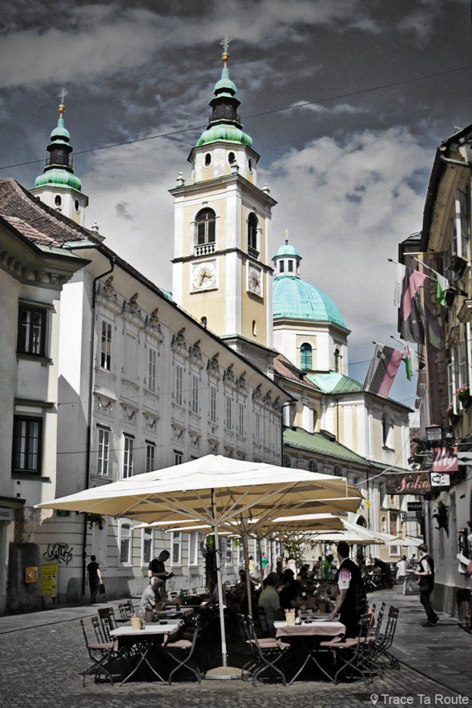 Terrasse de restaurant dans la rue Ciril-Metodov Trg et Cathédrale Saint-NicolasStolnica svetega Nikolaja de Ljubljana, Slovénie