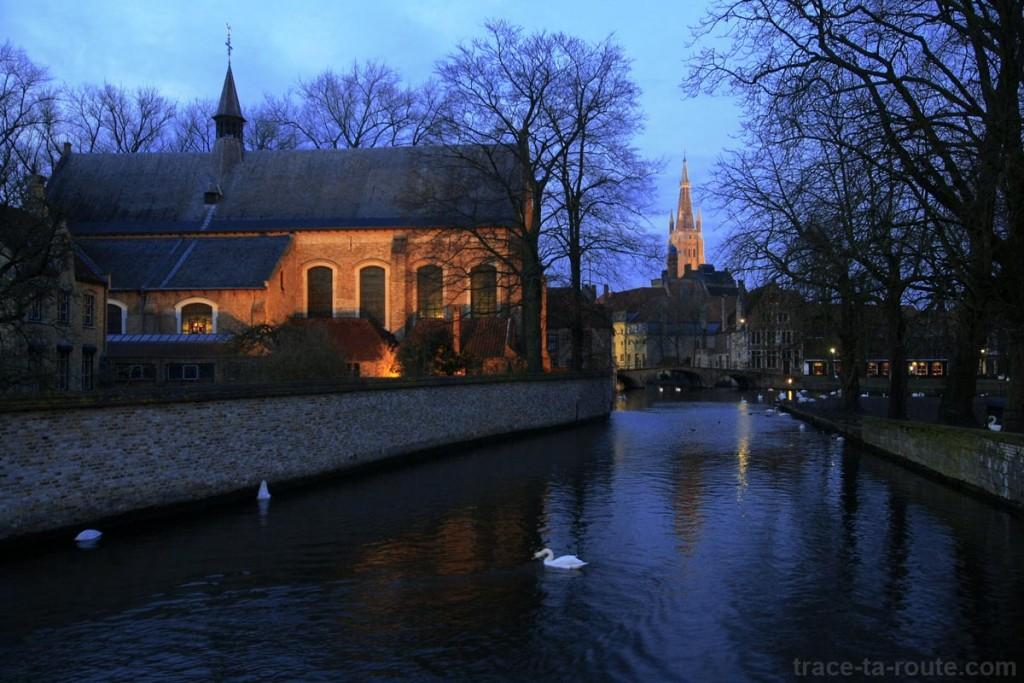 Église du Béguinage de Bruges au bord d'un canal, avec le clocher de l'Église Notre-Dame en fond