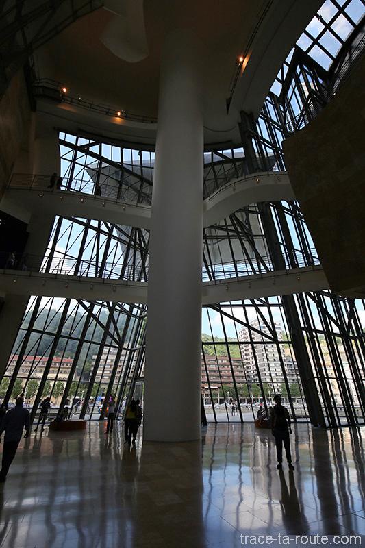 Intérieur architecture Musée Guggenheim Bilbao - Atrium, rampes passerelles et baie vitrée sur la ville