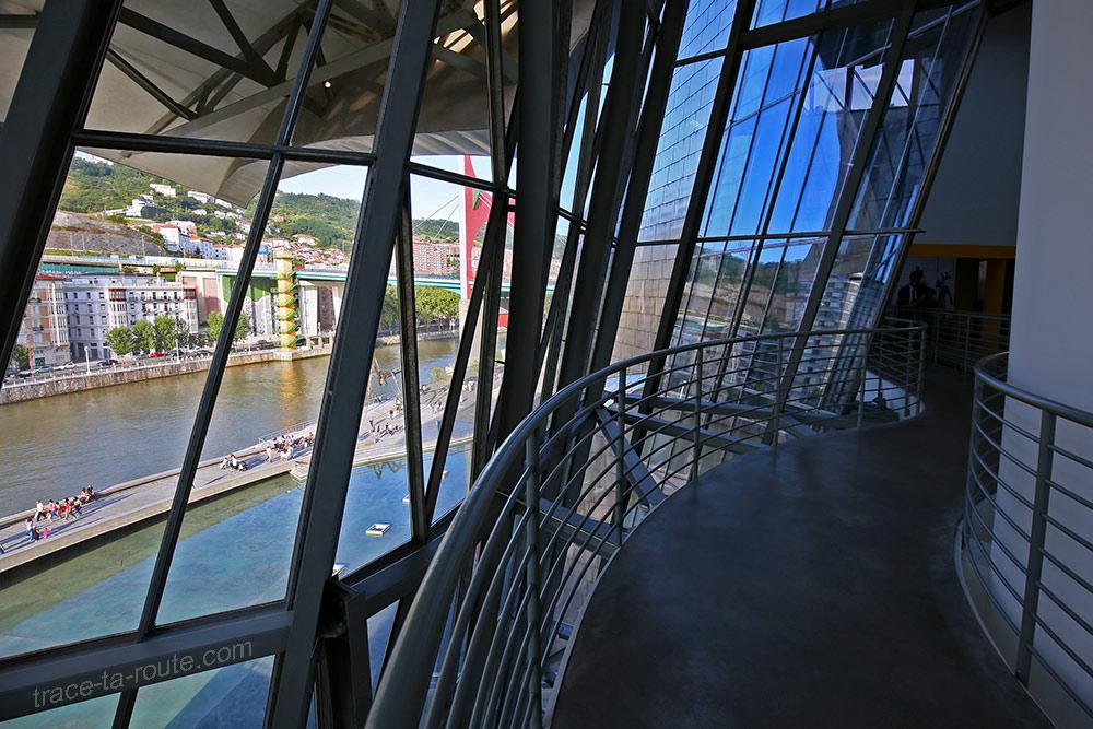 Intérieur architecture Musée Guggenheim Bilbao - rampes passerelles et Vue extérieure sur le fleuve Nervion par les baies vitrées