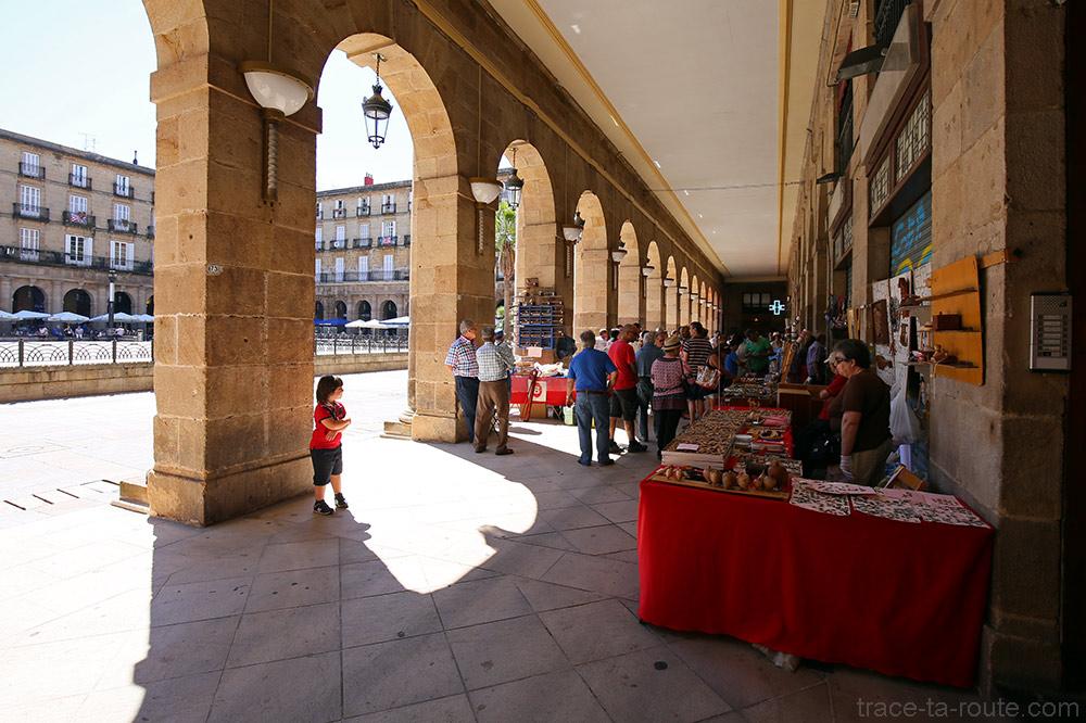 Braderie du dimanche de la Plaza Nueva de Bilbao avec les étals sous les arches