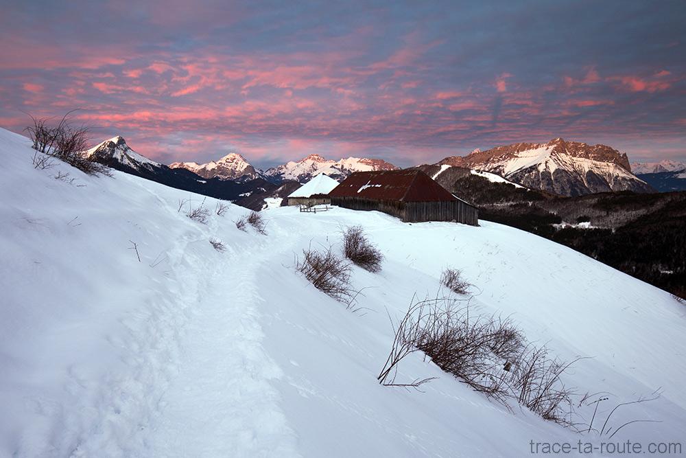 Ciel au coucher de soleil dans le Massif des Bauges avec Chalet de la Buffaz sous la neige en hiver