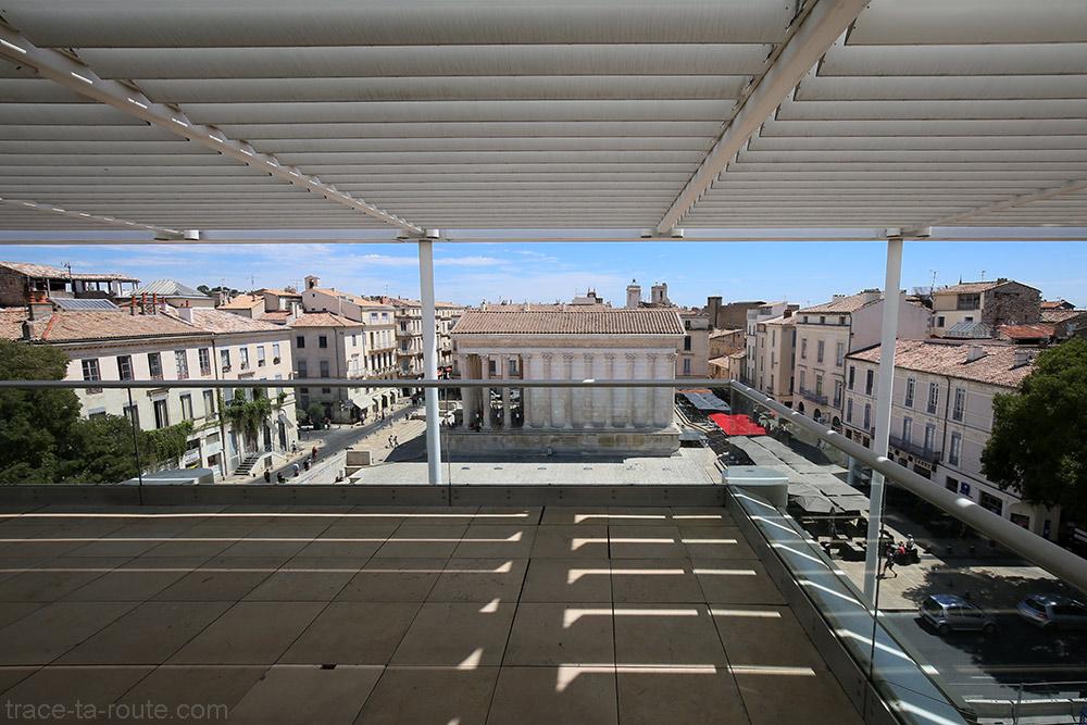 Vue sur la Maison Carrée depuis la terrasse du Carré d'Art de Nîmes - Restaurant Le Ciel de Nîmes sous les persiennes