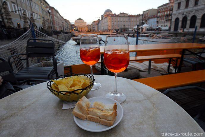 Aperitivo Apérol Spritz sur la terrasse du Caffè Rossini sur le Canal Grande de Trieste avec l'Église Sant'Antonio Nuovo en fond