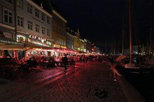 Canal de Nyhavn à Copenhague by night : terrasses sur le quai le soir et façades colorées (Danemark)