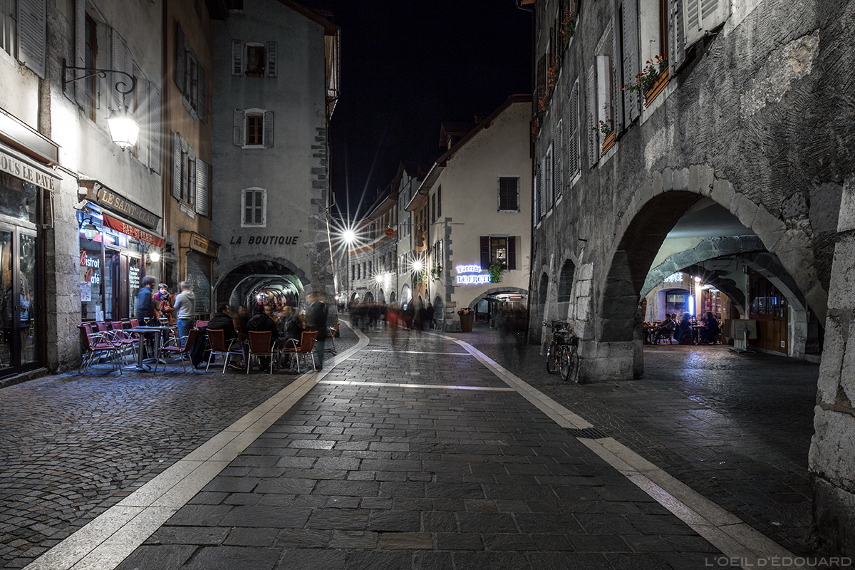 Rue Sainte-Claire la nuit dans la Vieille Ville d'Annecy avec les arcades et les terrasses © L'Oeil d'Édouard