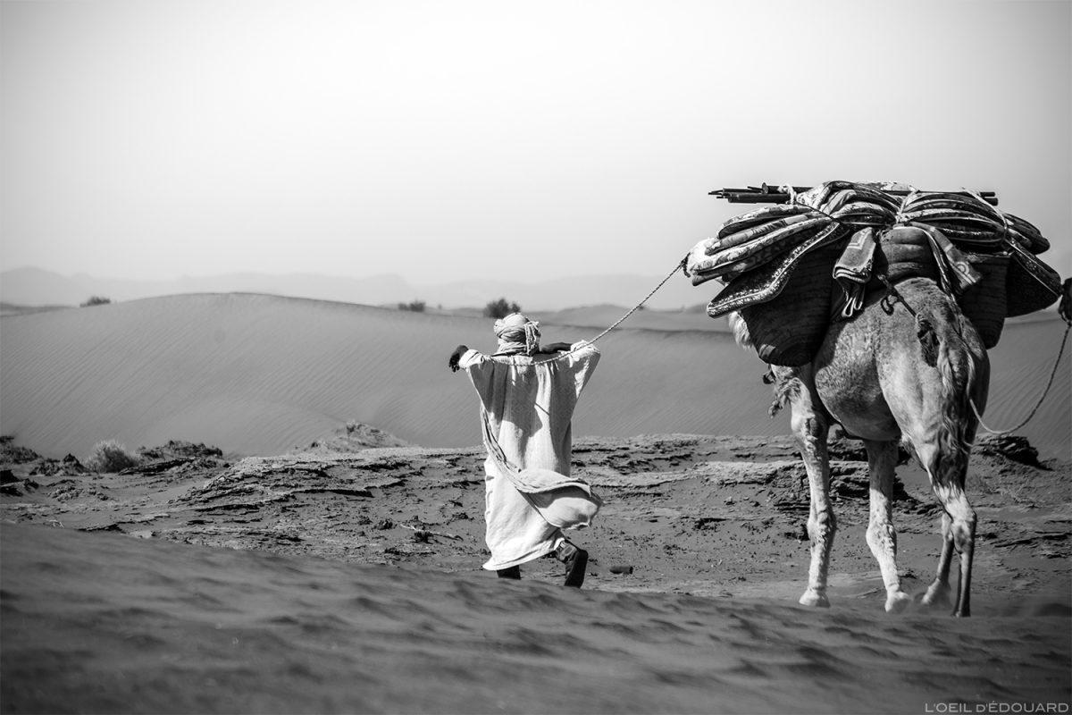 Nomade sahraoui marchant dans le Désert du Maroc avec un dromadaire © L'Oeil d'Édouard