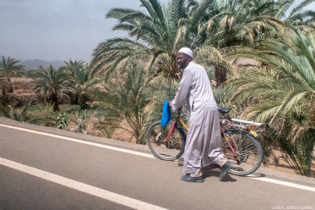 Homme en vélo sur le bord de la route N9 dans la Vallée du Draâ, Maroc