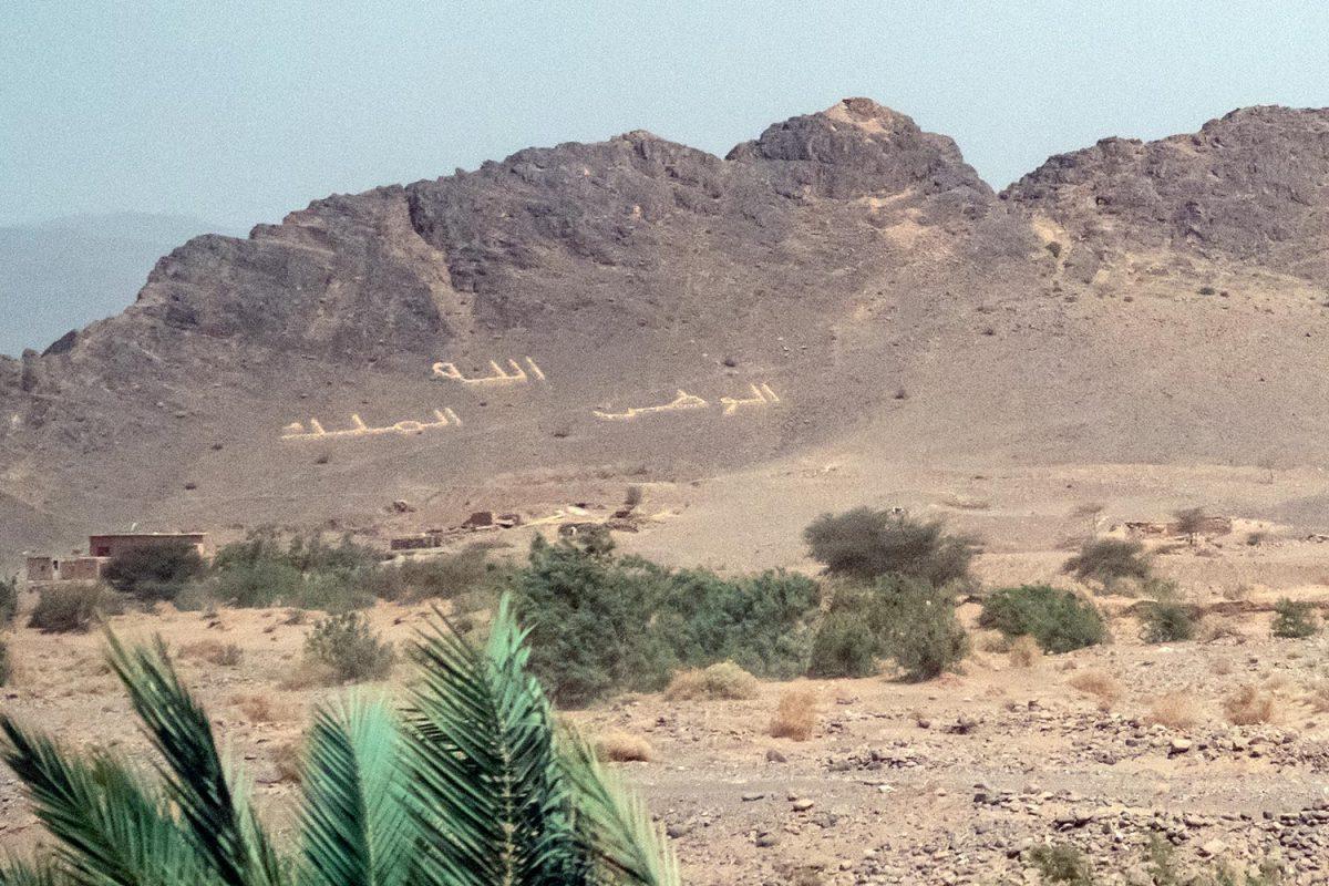 Écriture devise du Maroc sur la montagne au bord de la route N9 dans la Vallée du Draâ